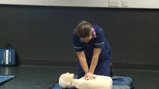 A nurse demonstrates CPR technique.
