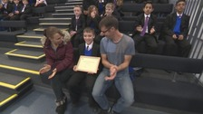Tyler receiving his award, with his mother and father.