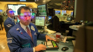 "Trader Michael Pistillo wears ""2013"" glasses celebrating New Year's Eve as he works on the floor of the New York Stock Exchange"