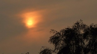 The blood red sun shining through the clouds and dust at Fordham Heath in Essex.