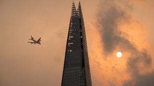 A plane flies past the Shard in central London, as the sky takes on an unusual orange colour caused by Storm Ophelia.