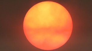 A red sun is not unusual when it low in the sky at sunset but less common in the middle of the day.