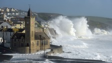 Huge waves break around a church in Porthleven, Cornwall, as Storm Ophelia hits the UK.