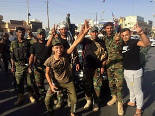 Iraqi security forces and volunteers celebrate after retaking Kirkuk