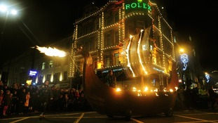 A jet of fire is seen behind a Viking longboat float in the parade