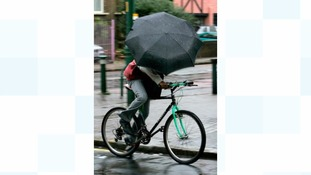 Commuters battle against the wind on their way to work