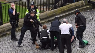 A police officer points a gun at terrorist Khalid Masood at Westminster.