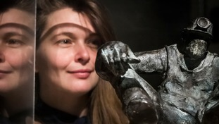 Gallery employee Kathryn Wilson views a bronze sculpture titled Miner by artist Alistair Brookes during a press preview of the Mining Art Gallery in Bishop Auckland, County Durham.