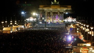 General overview shows people attending New Year celebrations at Brandenburger Tor gate in Berlin