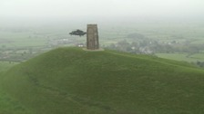 Navy helicopter hovers over Glastonbury Tor