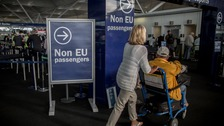 Passengers walk through a gate at London Stansted Airport.