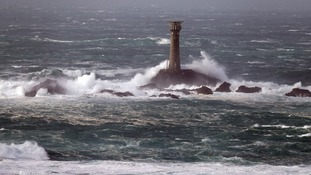 Waves crash around the Longships lighthouse off of Land's End in Cornwall.