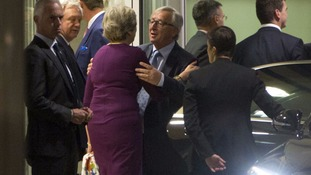 Theresa May and Jean-Claude Juncker greet each other at the dinner in Brussels.