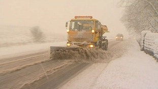 Snow plough clearing road