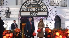 President Trump and First Lady Melania await trick-or-treaters at the White House.