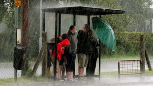 People shelter from the rain at a bus stop at Heather, Leicestershire in July