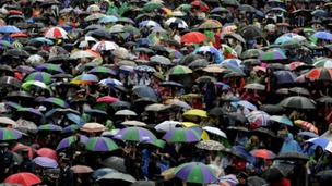 Wimbledon fans sheltered from the rain on Murray Mount in June.