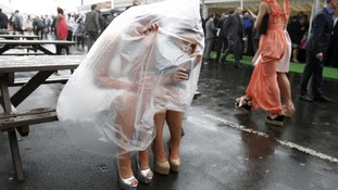 Two ladies shelter from the rain at the Grand National meeting at Aintree in April