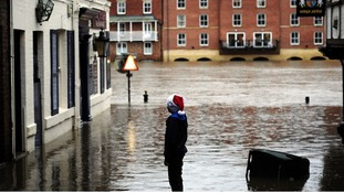 A young Christmas shopper looks at flood water in York city centre