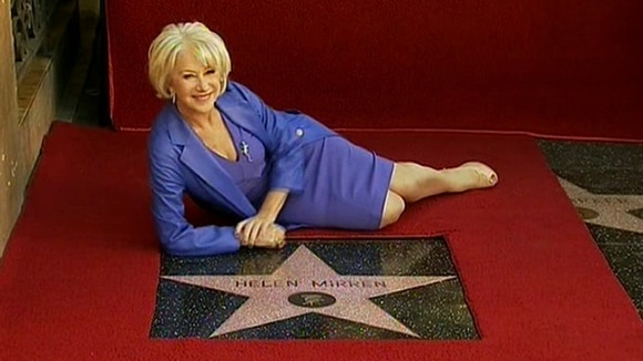 Helen Mirren posing with her star on the Hollywood Walk of Fame