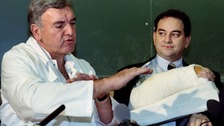 French surgeon Professor Jean-Michel Dubernard  makes a point near Clint Hallam's bandaged forearm
