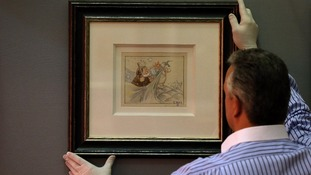 David Smith of Neptune Fine Art in Derbyshire, hangs an original artwork from Walt Disney's 'Snow White and the Seven Dwarfs' movie