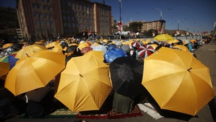 Pro-democracy protesters shield themselves from the sun with umbrellas during their protest