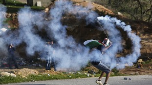 A masked Palestinian protester uses a sling to throw back a tear gas canister