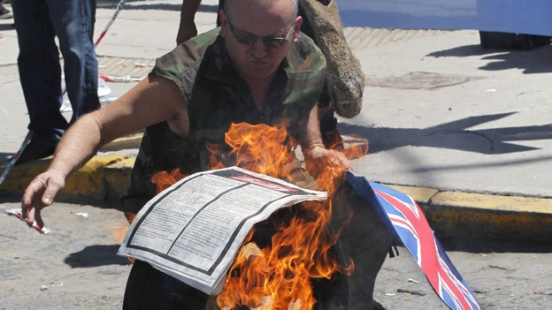 A protester sets fire to the paper with The Sun advert