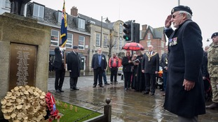 A member of the Royal British Legion salutes after laying a wreath at the war memorial during a service of remembrance at Royal Wootton Bassett.