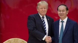 President Donald Trump and Vietnamese President Tran Dai Quang shake hands together during a State Dinner in Hanoi.