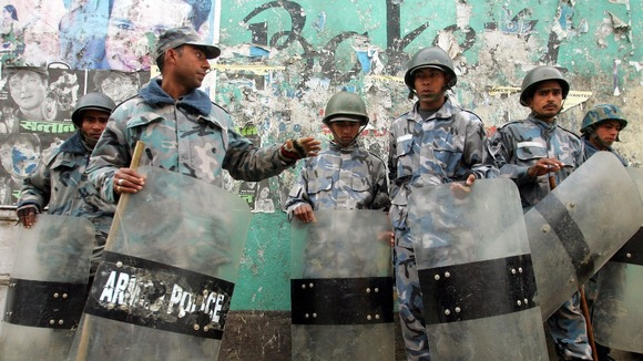Nepalese policemen take position on a street near the royal palace in Kathmandu in February 2005