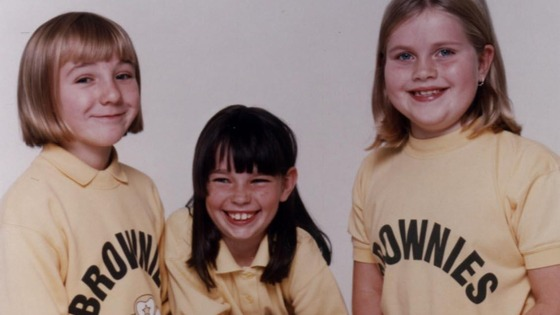 Brownies model their uniforms in 1990