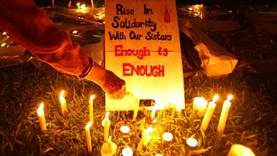 A participant lights a candle next to a sign during a vigil for the Indian rape victim
