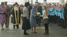The queen is hand a bouquet of flowers