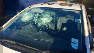 The police car's windscreens were damaged in the attack.