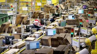 Staff label and package items in the on-site dispatch hall inside one of Britain's largest Amazon warehouses in Dunfermline.