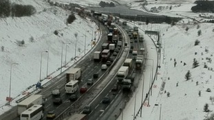 Miles of slow moving traffic in the snow on the M62 at Outlane in West Yorkshire