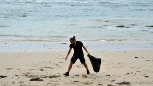 A man clears plastic litter from a beach.