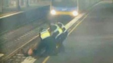 Police save woman from path of oncoming train