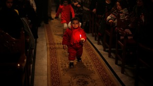 A Palestinian Greek Orthodox boy holds a candle as he attends Christmas services at the Saint Porfirios church in Gaza City