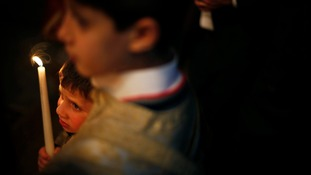 A Palestinian Greek Orthodox boy attends Christmas services at the Saint Porfirios church in Gaza City