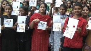 A group of students pose with a women's safety card.