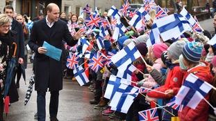 Schoolchildren greet Prince William as he arrives at auttasaari Comprehensive School in Helsinki.
