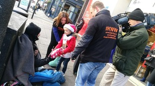 Frankie hands out parcels to the homeless.