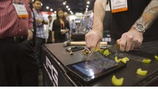 A demonstration of celery being sliced on top of a Kindle protected with an Invisible Phone Guard (IPG) at the CES