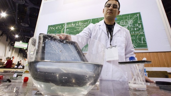 An iPad takes a dip into a bowl of water at the LifeProof booth at the CES