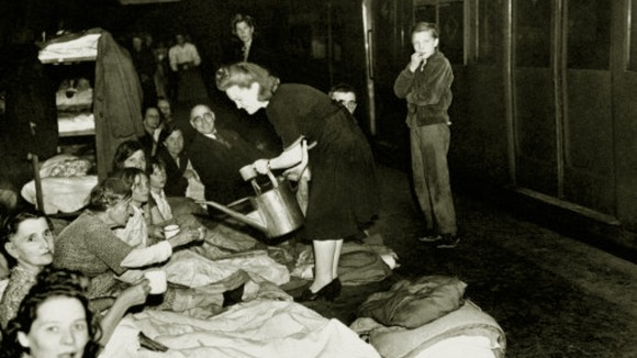 A woman dispensing water from a watering can as Londoners take shelter in the London Underground during the Blitz.