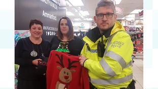 Staff from Peacocks, where the theft took place, with PC Steve Morris
