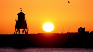 The sun rises over the lighthouse in South Shields